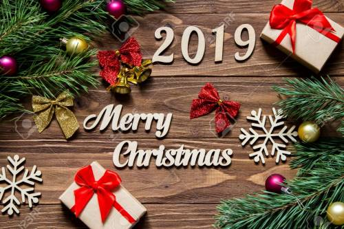 Merry Christmas 2019. Christmas gifts and tinsel on the wooden background